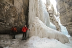 Jen in the Maligne Canyon Ice Walk - climbing out from behind a frozen waterfall